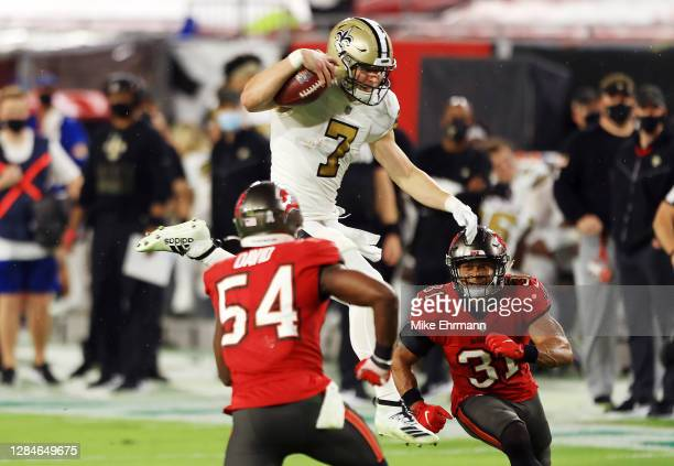 Taysom Hill of the New Orleans Saints attempts to hurdle Lavonte David and Antoine Winfield Jr. #31 of the Tampa Bay Buccaneers during the first half...