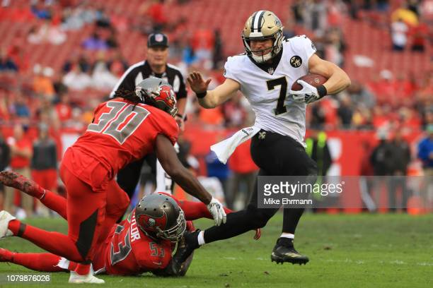 Taysom Hill of the New Orleans Saints breaks a tackle from Adarius Taylor of the Tampa Bay Buccaneers during the fourth quarter at Raymond James...