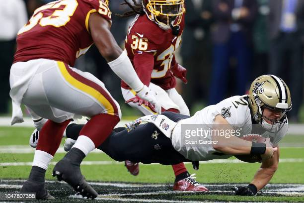 Taysom Hill of the New Orleans Saints dives with the ball as DJ Swearinger of the Washington Redskins and Zach Brown defend during the first half at...