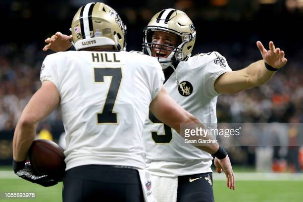 Taysom Hill of the New Orleans Saints reats with Drew Brees of the New Orleans Saints after scoring a touchdown during the second half against the...