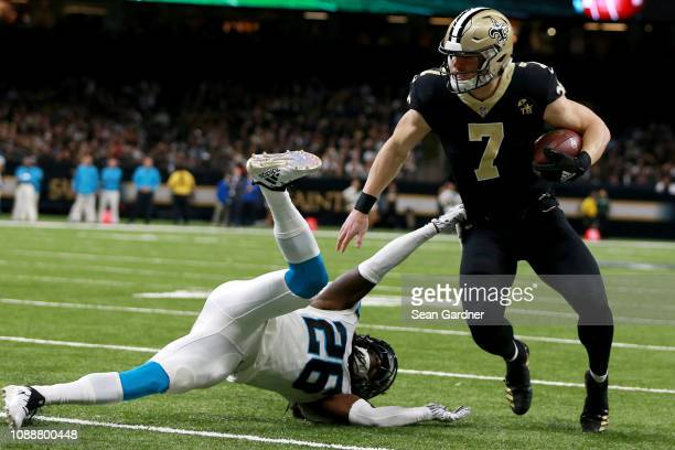 Taysom Hill of the New Orleans Saints runs the ball past Donte Jackson of the Carolina Panthers during a NFL game at the MercedesBenz Superdome on...