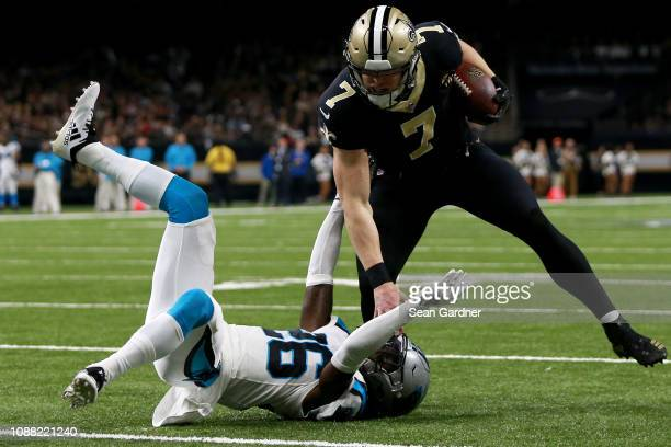 Taysom Hill of the New Orleans Saints runs with the ball as Donte Jackson of the Carolina Panthers defends during the second half during a NFL game...