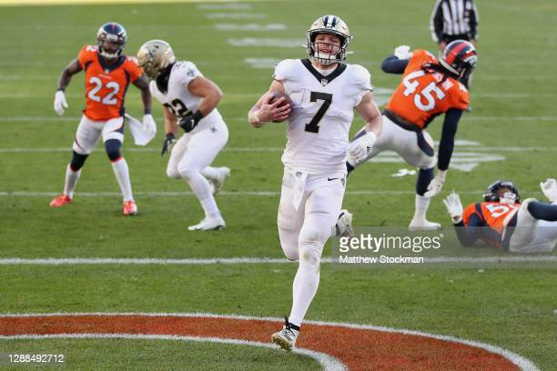 Taysom Hill of the New Orleans Saints rushes for a two yard touchdown during the second quarter of a game against the Denver Broncos at Empower Field...