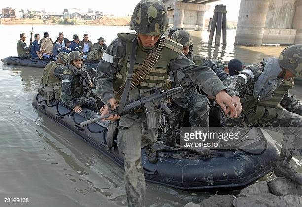 Taytay/Puerto Princesa, PHILIPPINES: Marines in full battle gear patrol disembark after joining police in a raid on a suspected terrorist hideout in...