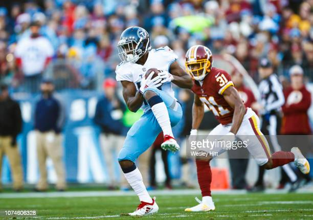 Taywan Taylor of the Tennessee Titans catches a pass from Marcus Mariota while defended by Fabian Moreau of the Washington Redskins during the first...