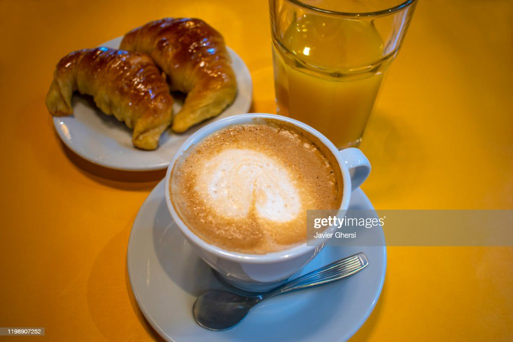 Taza de café con leche, medialunas de manteca y vaso de jugo de naranja exprimido : Stock Photo