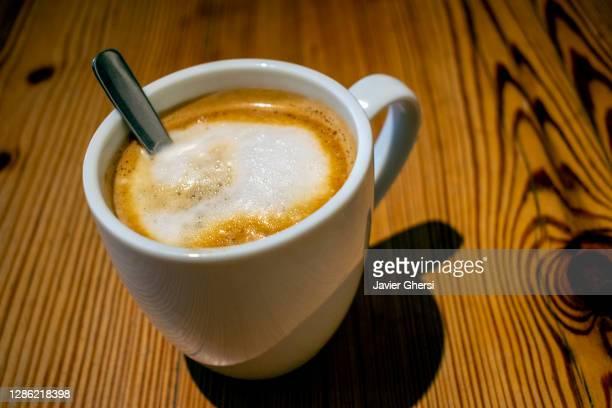 taza de café con leche sobre mesa de madera - taza de café stock pictures, royalty-free photos & images