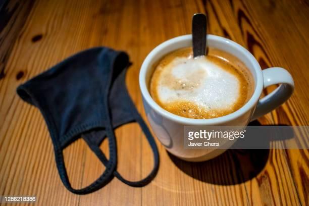 taza de café con leche y tapaboca (barbijo) sobre mesa de madera - taza de café stock pictures, royalty-free photos & images
