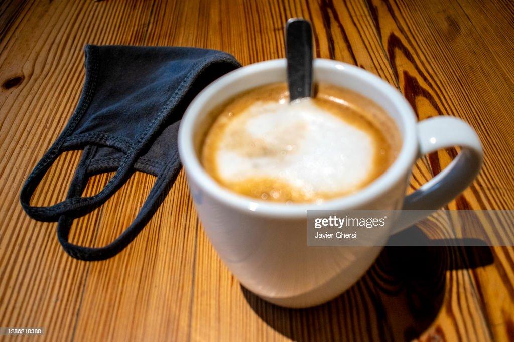 Taza de café con leche y tapaboca (barbijo) sobre mesa de madera : Stock Photo
