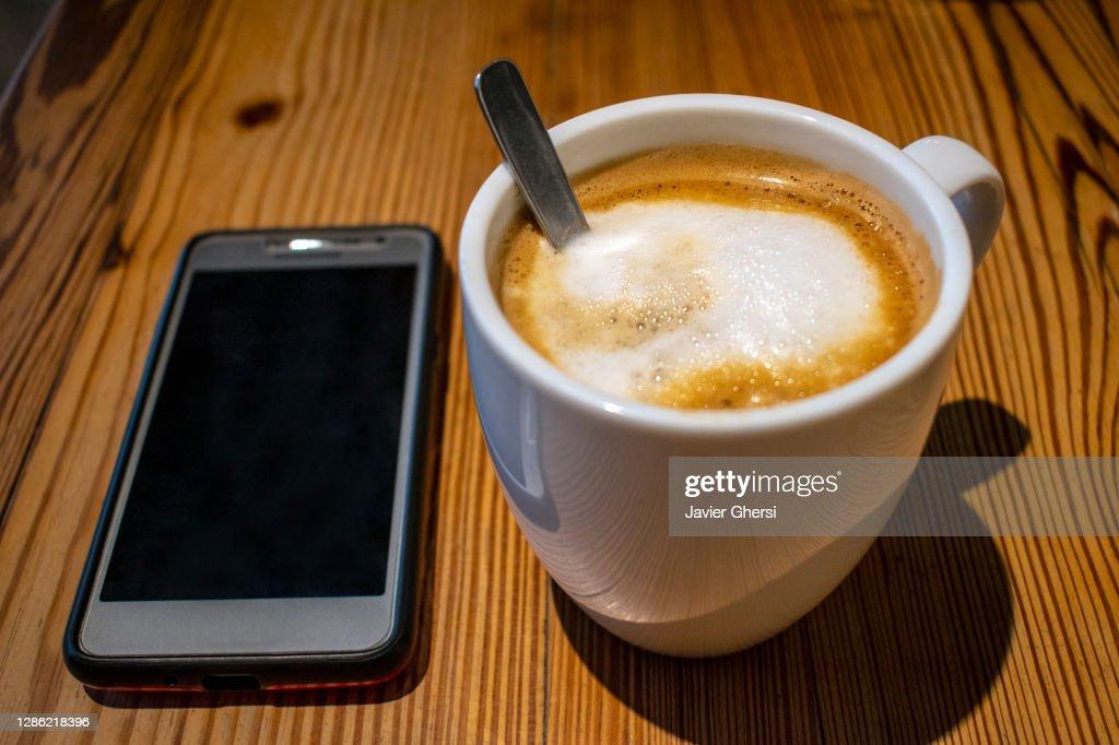 Taza de café con leche y teléfono celular sobre mesa de madera : Stock Photo