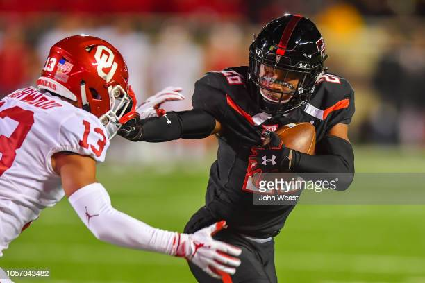 Ta'Zhawn Henry of the Texas Tech Red Raiders gets past Tre Norwood of the Oklahoma Sooners during the first half of the game on November 3 2018 at...