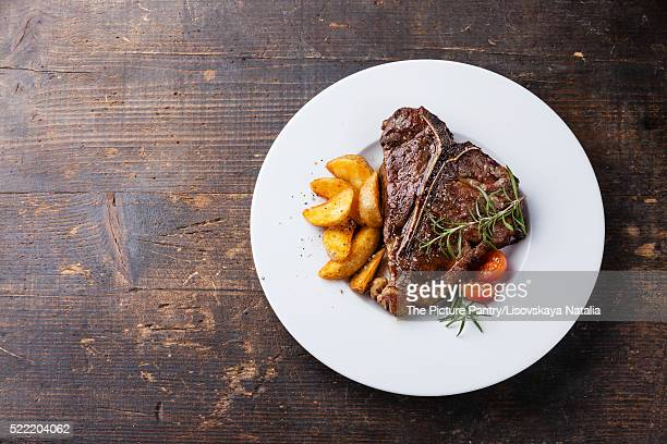 T-Bone Steak with roasted potato wedges on white plate on wooden