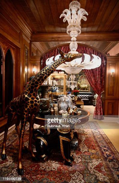 Tchotchke a glimmering chandelier lifesized giraffes and vintage carpets amidst Chinese African and Indian art and design elements make up the...