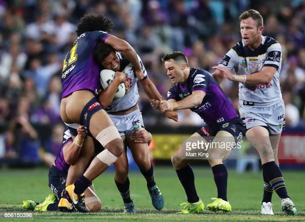 Te Maire Martin of the Cowboys is tackled by Felise Kaufusi of the Storm during the 2017 NRL Grand Final match between the Melbourne Storm and the...