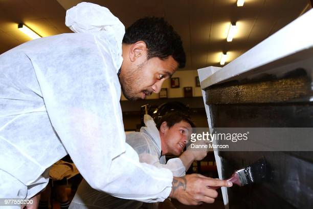 Te Toiroa Tahuriorangi and Matt Todd of the All Blacks help paint the Pirates Rugby Club's newly built pirate ship stage during an New Zealand All...