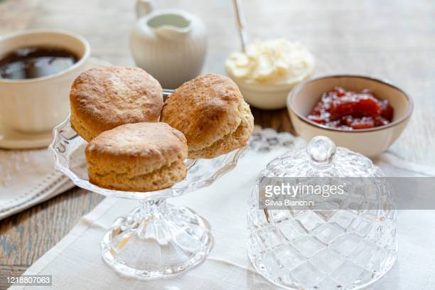 tea and scones with strawberry jam and clotted cream - english culture stock pictures, royalty-free photos & images