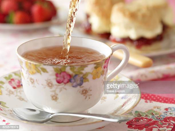 Tea being poured into a teacup at afternoon tea with scones