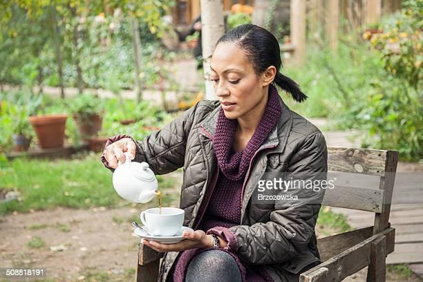 Tea break - woman drinking tea in garden (London, UK)