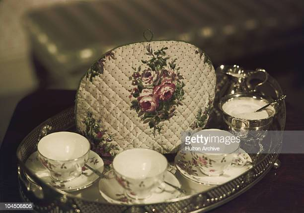 A tea cosy on a tray with a sugar bowl cups and saucers circa 1950