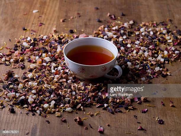Tea cup amidst herbs on wooden table