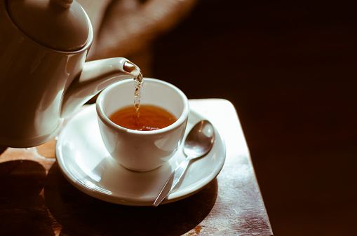 Tea cup on saucer, with tea being poured, 466073662