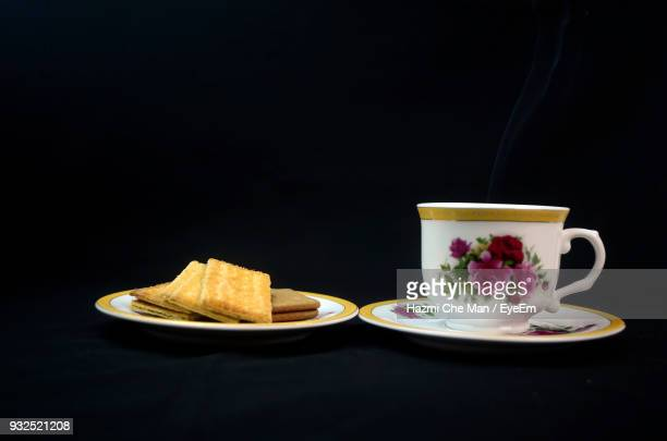 tea cup with cookies against black background - frische stockfoto's en -beelden