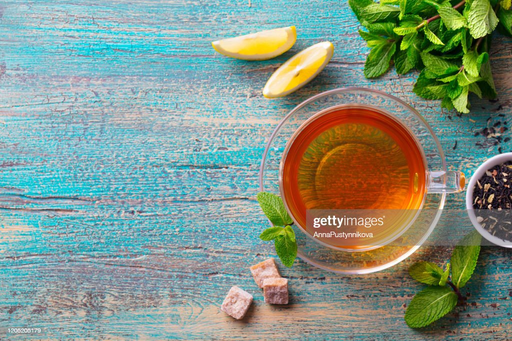 Tea cup with mint leaf and lemon. Wooden background. Copy space. Top view. : Stock Photo