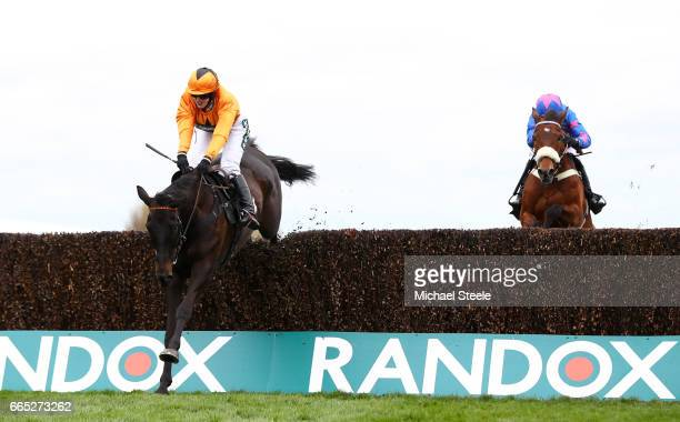 Tea for Two ridden by Lizzie Kelly passes Cue Card ridden by Paddy Brennan on it's way to winning the Betway Bowl Chase duering the Randox Health...