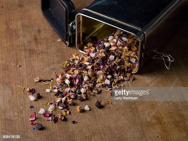 Tea herbs spilling out from container on table