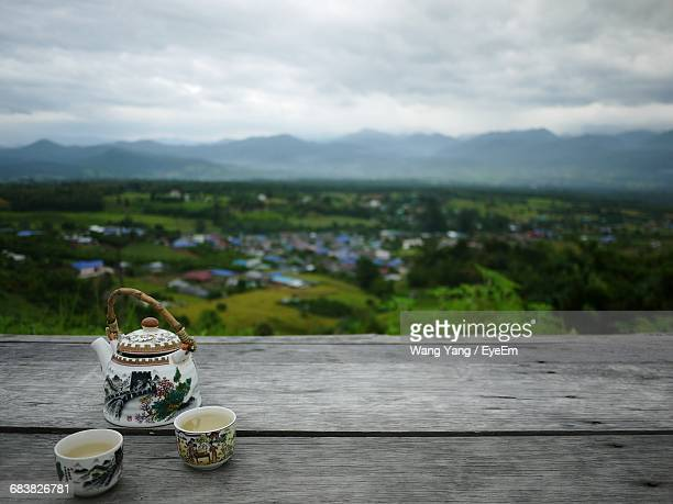 Tea Kettle And Cups On Wooden Table Overlooking Landscape