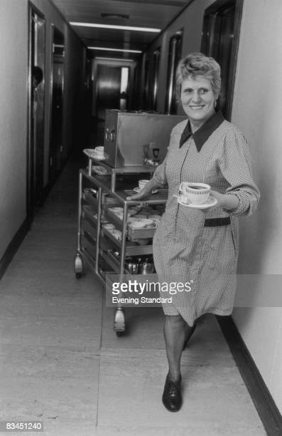 Tea lady Jessie Corbyn pulls her trolley along a corridor at the Britannia House office building in Hammersmith, west London, 13th November 1980.