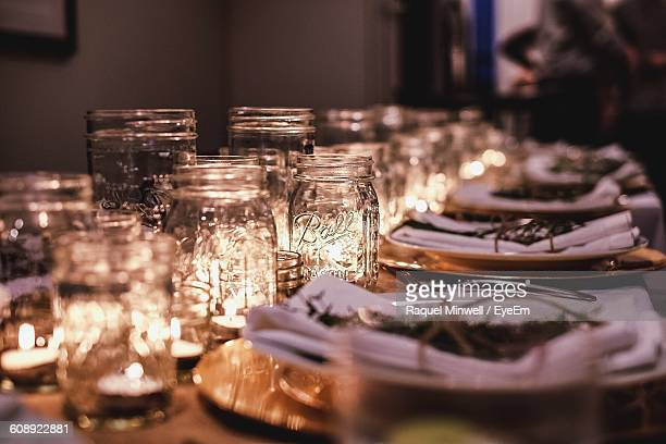 Tea Light Candles In Glass Jars By Plates Arranged On Table