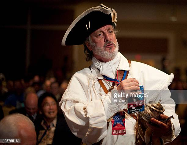 Tea Party activist William Temple holds up his Michele Bachmann badge as he talks with other attendees at the Family Research Council's Values Voter...