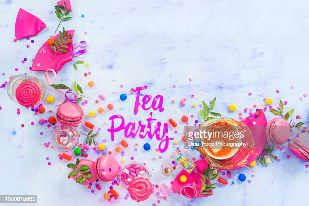 Tea party concept with paper text, candies, sweets, confetti, macarons and dynamic tea splash....