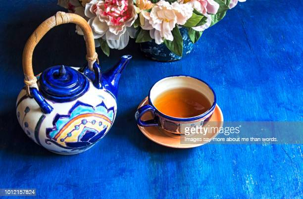 A tea pot, a cup of tea and flower arrangement over a blue background.