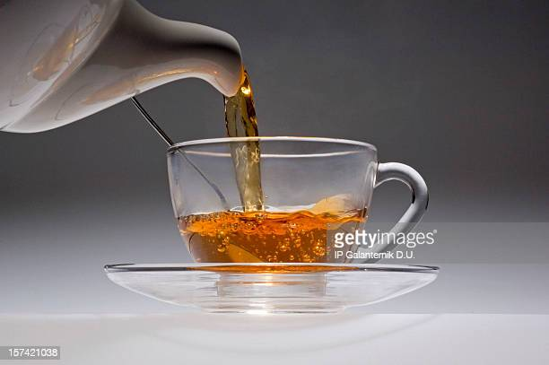 Tea pouring from a white china pot into glass cup.