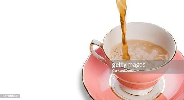 Tee eingießen in Tasse und Untertasse aus Porzellan, isoliert auf weiss