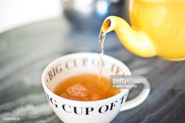 Tea pouring into teacup from teapot