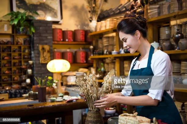 Tea room owner organizing flower