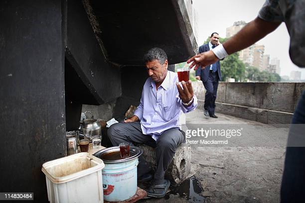 A tea seller works under an overpass in the wealthy area of Zamalek on May 27 2011 in Cairo Egypt Protests in January and February brought an end to...