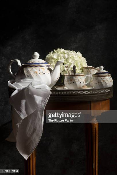 A tea service set on a table, on a dark background