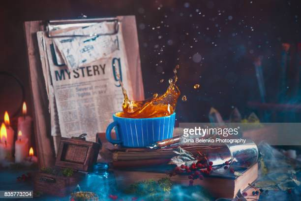Tea splash in a ceramic cup on a wooden background with candles, mystery newspaper clips, books, leaves and moss