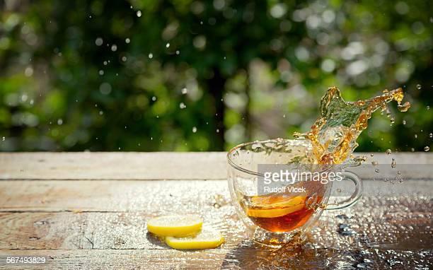 Tea splashing from glass cup, fallen lemon slice