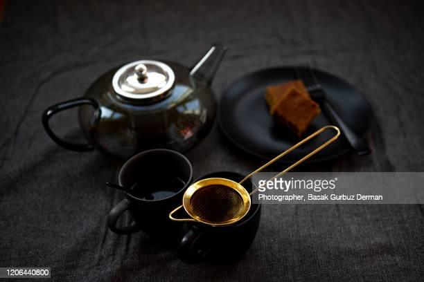 tea, teapot, tea cup and golden tea strainer - english teapot stock pictures, royalty-free photos & images