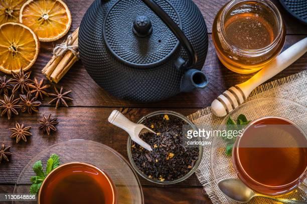 tiempo del té: taza de té, palillos de la canela, anís, anaranjado secado en la tabla de madera - hoja te verde fotografías e imágenes de stock