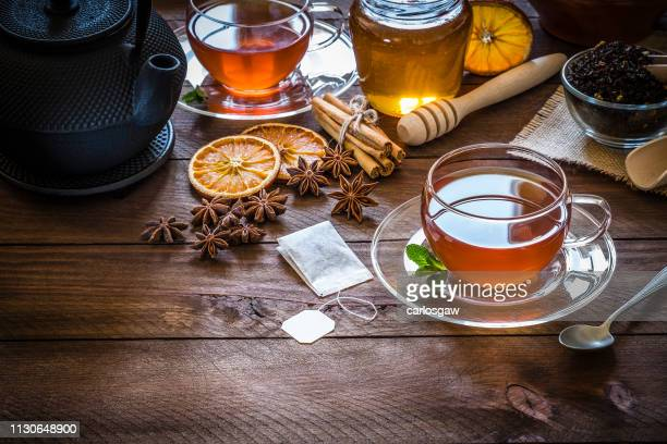 tea time: cup of tea, cinnamon sticks, anise, dried orange on wooden table - tea leaves stock photos and pictures