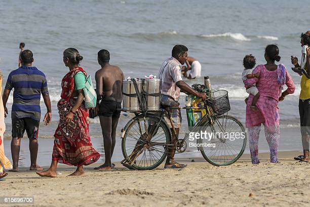 Tea vendor pushes a bicycle as visitors look out to sea at Velankanni Beach in Nagapattinam, Tamil Nadu, India, on Saturday, Oct. 15, 2016. India's...