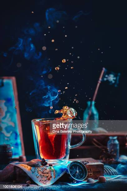 Tea with a tornado inside. Sea still life with a pirate flag, compass, and map. Action food photography with steam and tea splash