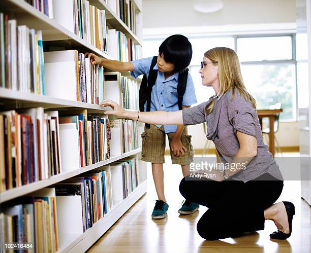 teacer helping boy select book in library