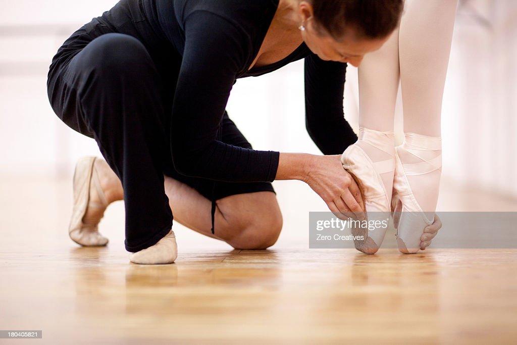Teacher adjusting foot position of ballerina : Stock Photo